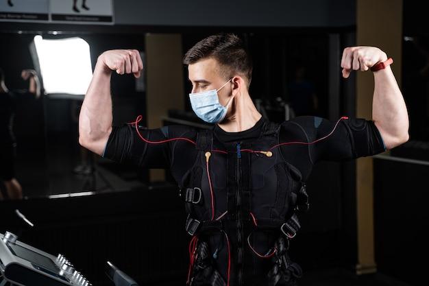 Homme en costume ems et masque médical dans une salle de sport