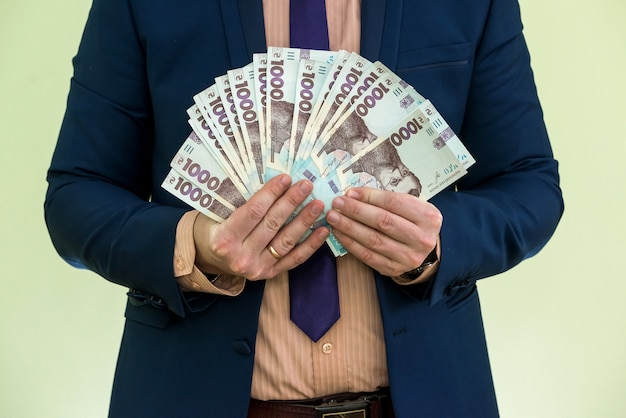Un homme en costume avec un énorme tas d'argent ukrainien. 1000 hryvnia. uah.