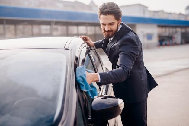 Homme en costume essuyant la fenêtre sur sa voiture.