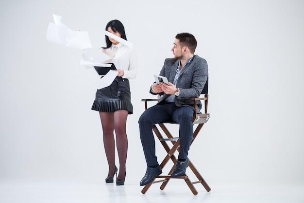 Un homme en costume est assis sur une chaise noire avec une tablette et une femme jette des documents. les futurs hommes d'affaires sont nerveux et parlent d'un nouveau projet. partenaires commerciaux sur fond blanc.