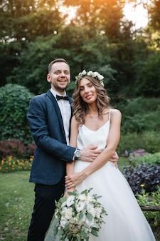 Un homme en costume étreignant sa petite amie à l'extérieur, la mariée et le marié le jour de son mariage