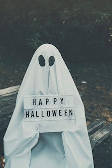 Homme en costume fantôme assis sur un banc et tenant une tablette
