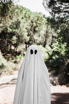 Homme en costume de fantôme debout dans la forêt