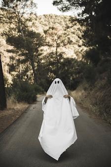 Homme en costume fantôme avec des mains visibles sur la route de la campagne