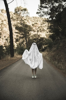Homme en costume fantôme sautant sur une route de campagne