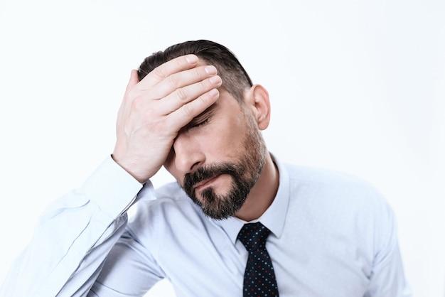 Un homme en costume ferma les yeux de la douleur.