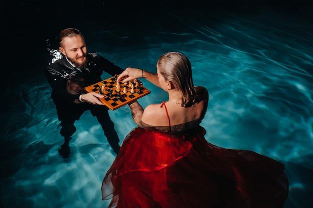 Un homme en costume et une fille en robe rouge jouent aux échecs sur l'eau de la piscine.