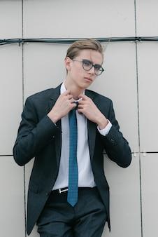 Un homme en costume gris et cravate bleue pose.