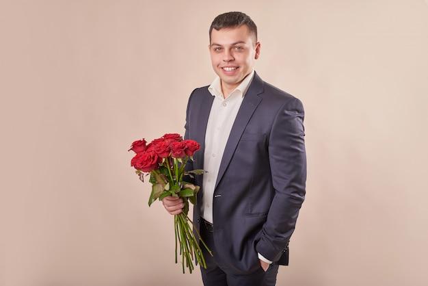Homme en costume gris avec roses rouges