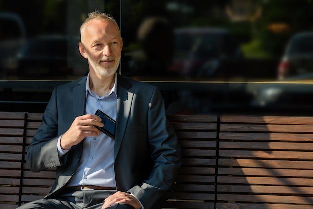 L'homme en costume gris avec un smartphone assis sur un banc.