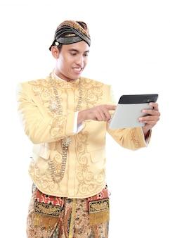 Homme avec costume java traditionnel à l'aide de tablet pc