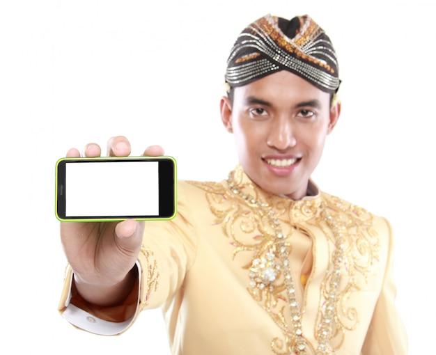 Homme avec costume java traditionnel à l'aide de téléphone portable