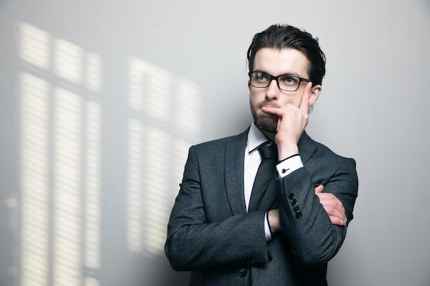 L'homme en costume et lunettes pense au mur gris