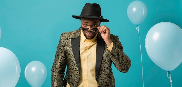 Homme en costume et lunettes de soleil à la fête