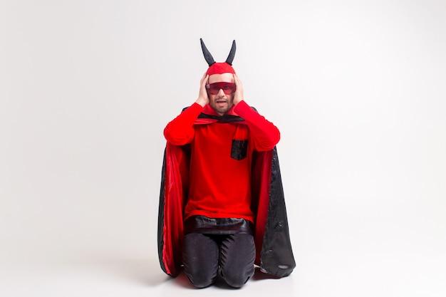 Homme en costume de mascarade diable posant.