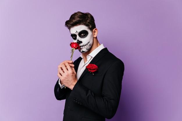 Un homme en costume de mascarade renifle une grande fleur rouge et regarde mystérieusement la caméra.