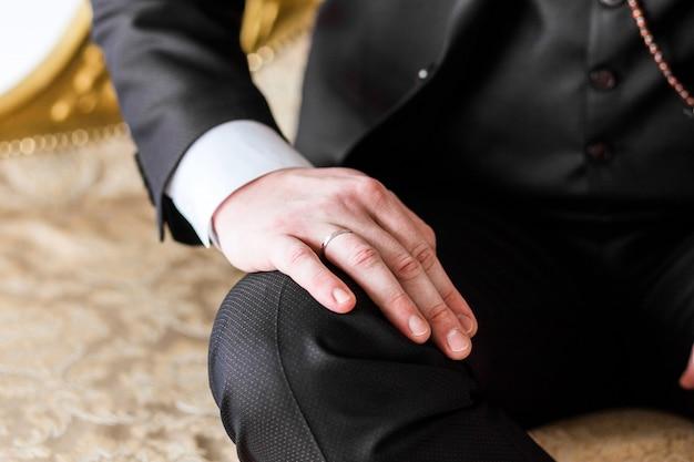 L'homme en costume a mis sa main sur son genou