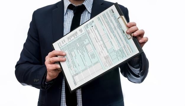 Homme en costume montrant 1040 formulaire d'impôt sur le presse-papiers isolé sur blanc