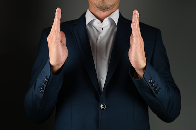 Un homme en costume montre la taille avec ses mains. photo de haute qualité