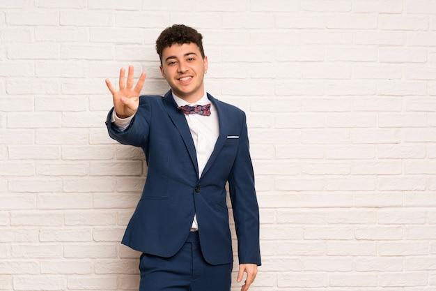 Homme en costume et noeud papillon heureux et comptant quatre avec les doigts