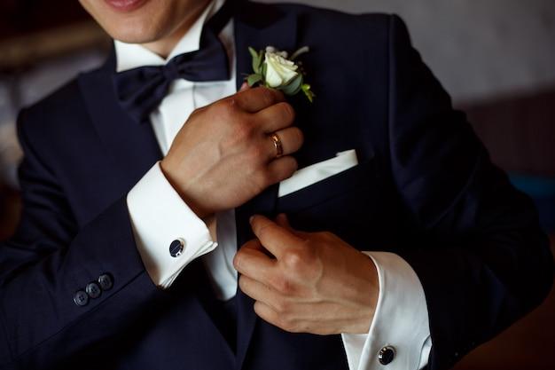 L'homme en costume noir et chemise blanche corrige la boutonnière de près. le marié avec une boutonnière. rencontre et matinée du marié. hansome guy en costume sombre et chemise blanche corrige la boutonnière