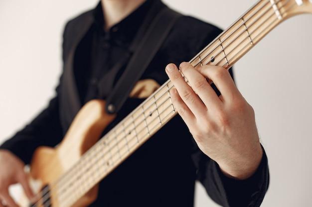 Homme en costume noir debout avec une guitare