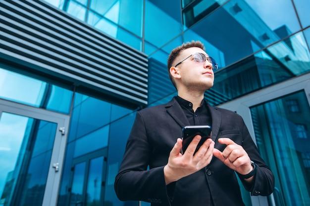 L'homme en costume noir du centre d'affaires moderne en verre. homme d'affaires confiant, parler au téléphone, marchant devant l'architecture moderne. portrait d'un homme d'affaires souriant