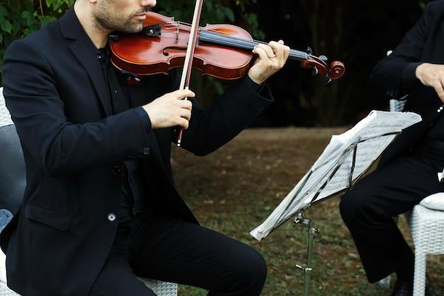 Homme en costume noir joue du violon