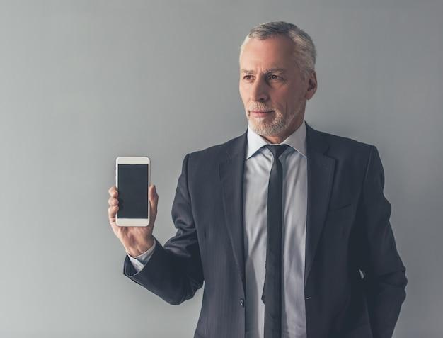 Homme en costume officiel montre un smartphone