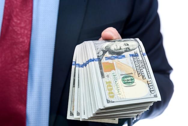 Homme en costume offrant des billets en dollars close up