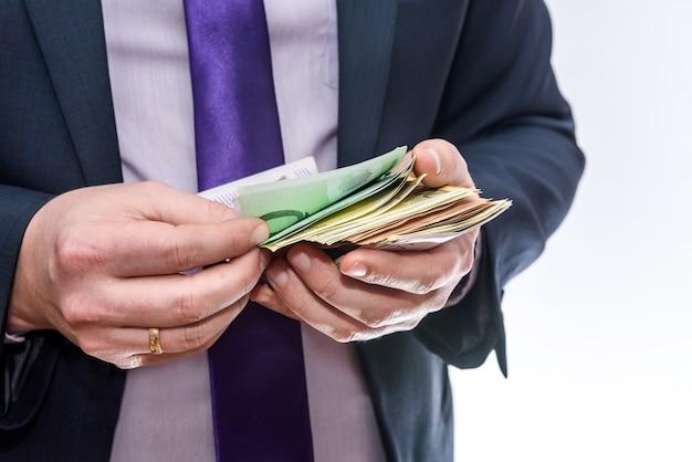 Homme en costume offrant des billets en euros close up