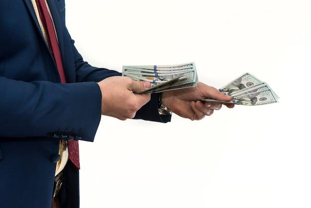 Un homme en costume offre un pot-de-vin pour un produit ou un service. homme d'affaires détient et donne des dollars. corruption ou salaire.