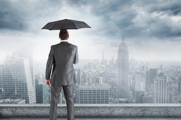 Homme en costume et parapluie regardant la ville