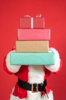 Homme en costume de père noël tenant des cadeaux