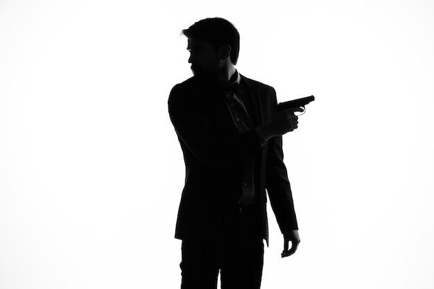 L'homme en costume avec un pistolet en main crime geste de la main fond clair
