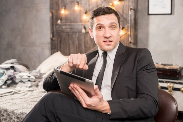 Homme en costume pointant vers la tablette