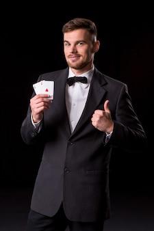 Homme en costume posant avec des cartes pour le jeu sur fond noir