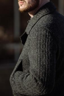 Un homme en costume et pull pose dans la rue.