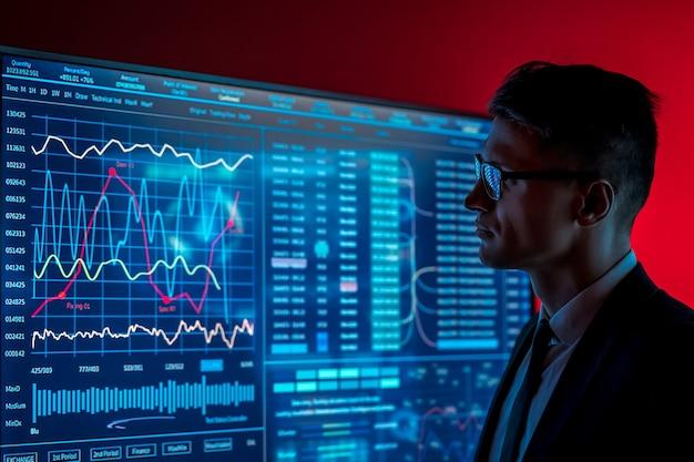 L'homme en costume regardant sur un écran bleu avec quelques données