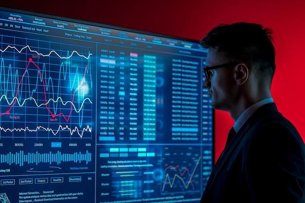 L'homme en costume regarde sur un écran bleu avec quelques données