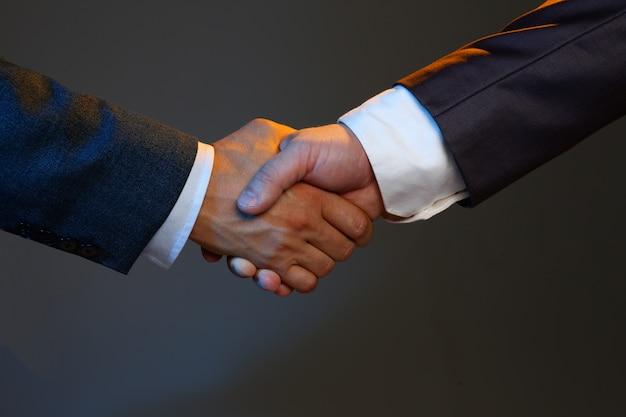 Homme en costume serrer la main comme bonjour en gros plan de bureau