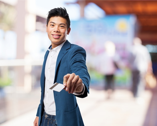 Homme en costume souriant avec une carte de crédit en main