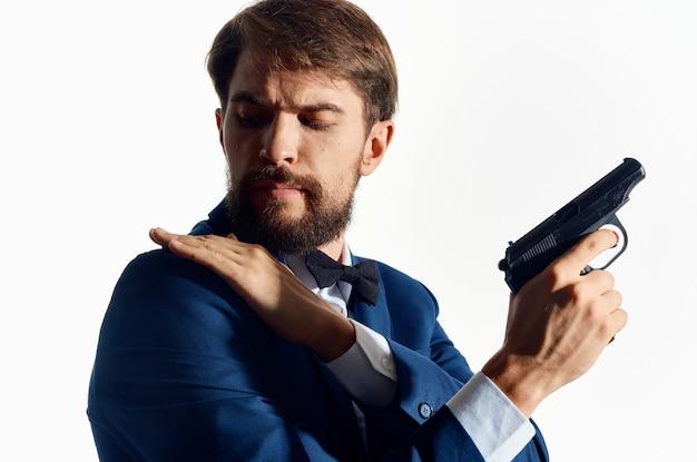 Homme en costume tenant une arme de poing