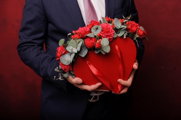 Homme en costume tenant dans une main une boîte rouge de roses