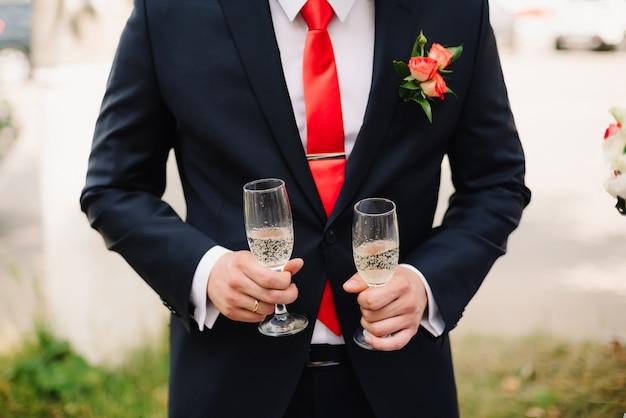 Homme en costume tenant deux verres de champagne