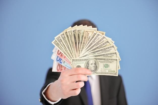 Homme en costume tenant fan de billets en dollars et en euros sur bleu