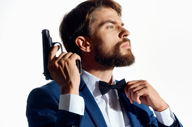 Homme en costume tenant un gangster de style de vie pistolet mafia close-up.