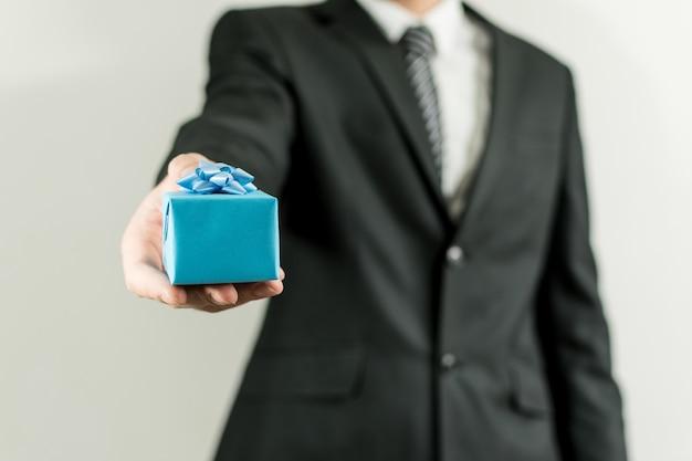 Homme en costume tenant une petite boîte cadeau bleue