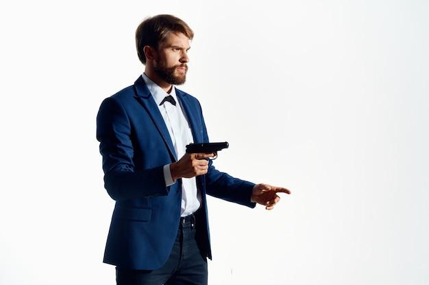Homme en costume tenant pistolet gangster mode de vie crime fond isolé.
