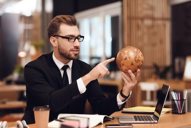 Un homme en costume tient un globe entre ses mains.